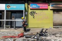 A woman cleans debris outside the Dube Village mall in Durban, South Africa, on July 17, after several days of looting and unrest. (Guillem Sartorio/AFP/Getty Images)