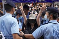 """A woman raises her hands in a symbol of """"Five demands, not one less"""" at Causeway Bay after police denied permission for a protest rally during the 24th anniversary of the former British colony's return to Chinese rule, on the 100th founding anniversary of the Communist Party of China, in Hong Kong on Thursday. (Lam Yik/Reuters)"""