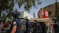 Supporters of Kais Saied seut up the Tunisian flag on the roof of a store in front of the riot police, during a demonstration held in front of the building of the Tunisian parliament in Bardo, in the capital Tunis, Tunisia, on July 26, 2021. Chedly Ben Ibrahim / NurPhoto via AFP