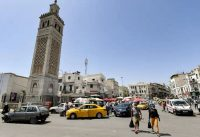 People pass the Sidi Bashir mosque in the Bab el-Fellah area of Tunisia's capital Tunis on July 28. (Fethi Belaid/AFP/Getty Images)