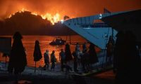 People board a ferry during evacuation as a wildfire burns in the village of Limni, on the island of Evia, Greece, on Friday. Photograph: Nikolas Economou/Reuters