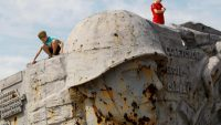 Boys stay on top of the war memorial complex Savur-Mohyla, damaged in the recent conflict, outside the rebel-held city of Donetsk, Ukraine 8 September 2020. REUTERS/Alexander Ermochenko