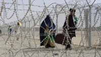 Afghan nationals walk along a fenced corridor after crossing into Pakistan through the Pakistan-Afghanistan border crossing point in Chaman on 28 August 2021. AFP