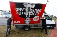 Workers remove election campaign poster in Cologne, Germany, on Sept. 27. (Thilo Schmuelgen/Reuters)