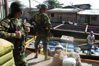 Integrantes de las fuerzas especiales del Ejército colombiano vigilan un bote que carga barriles para ser usados en laboratorios de cocaína.Kaveh Kazemi / Getty Images