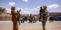 A local woman photographs a US soldier with her children while on patrol near the Turkish border in northeastern Syria. Photo by John Moore/Getty Images.