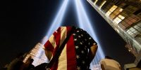 A man wearing an American flag shirt visits the Tribute In Lights in Lower Manhattan on September 11, 2021 in New York City. Photo by Alexi Rosenfeld/Getty Images.