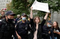 """Police detain a journalist holding a poster that reads """"We will not stop being journalists"""" during picketing in Moscow on Aug. 21. (Denis Kaminev/AP)"""