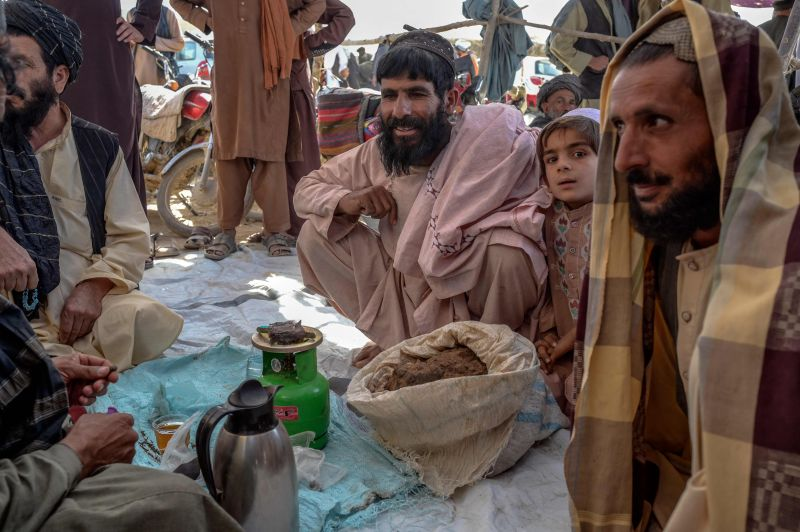 People gather around bags containing heroin and hashish at a drug market in Kandahar, Afghanistan, on Sept. 24. (Bulent Kilic/AFP/Getty Images)