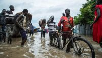 Displaced people walk with their belongings in a flooded area after the Nile river overflowed after continuous heavy rain which caused thousands of people to be displaced in Bor, central South Sudan, on 9 August 2020. Akuot Chol / AFP