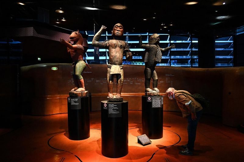 A visitor looks at some of the royal treasures of Abomey, looted during the colonial era, now on display at the Quai Branly Museum in Paris and due to be returned to Benin in the coming months. © Christophe Archambault / AFP