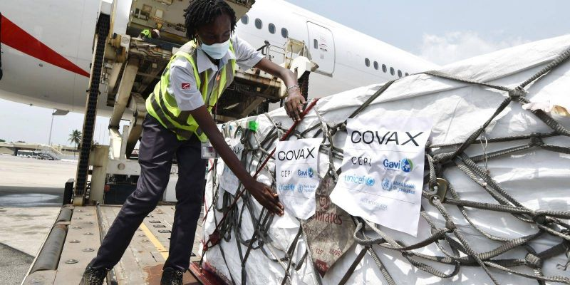 Unloading a shipment of AstraZeneca COVID-19 vaccine in Abidjan, Ivory Coast sent using the COVAX global scheme to procure and distribute inoculations for free. Photo by SIA KAMBOU/AFP via Getty Images.
