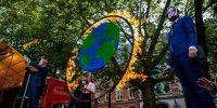 A group of activists is setting on fire a circle that represents the Earth, while they are dressing like politicians, during the Global Climate Strike organized in Utrecht, on 24 September 2021. Photo by Romy Arroyo Fernandez/NurPhoto via Getty Images.