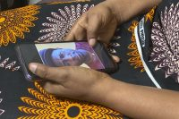 A person in the Congo holds a phone displaying a photo of former WHO doctor Boubacar Diallo, who has been accused of pressuring a woman to have sex with him for a job. (Kudra Maliro/AP)
