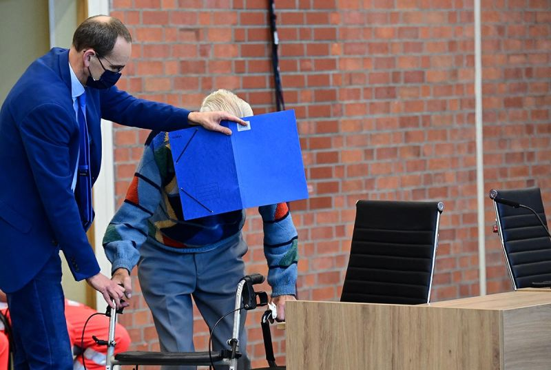 Defendant Josef Schütz gets help from his lawyer to hide his face as he arrives for his trial in Brandenburg an der Havel, northeastern Germany, on October 7, 2021. The 100-year-old former concentration camp guard is the oldest person yet to be tried for Nazi-era crimes. © Tobias Schwarz / AFP